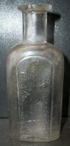 Image of 1999.048.176 - A.R.Kirkpatrick Medicine Bottle recovered from City Centre Plaza, c. 1870-1920. This bottle is oval shaped with a flat front face in cross section and it has narrowed slightly from shoulder to base. The rim has prescription finish which is narrow (vertically) and the outside surface distinctly tapers in from the top surface of the finish to bottom. The front side of bottle is embossed vertically (in a plate) with A.K.KIRKPATRICK/ PIONEER DRUG STORE/REDWOOD CITY. A .875 inch short and narrow neck flares out .75 inches shoulders to a 2.75 inch body. The bottle is clear and shows evidence of glass machine manufacture.
