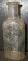Image of 1999.048.185 - A.R.Kirkpatrick Medicine Bottle recovered from City Centre Plaza, c. 1870-1920. This bottle is oval shaped with a flat front face in cross section and it has narrowed slightly from shoulder to base. The rim has prescription finish which is narrow (vertically) and the outside surface distinctly tapers in from the top surface of the finish to bottom. The front side of bottle is embossed vertically (in a plate) with A.K.KIRKPATRICK/ PIONEER DRUG STORE/REDWOOD CITY. A .875 inch short and narrow neck flares out .5 inches shoulders to a 2.25 inch body. The bottle is clear and shows evidence of glass machine manufacture.
