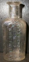 "Image of 1999.048.200 - Will Frisbie Medicine Bottle recovered from City Centre Plaza, c. 1880-1920. This bottle is oval shaped with a flat front face in cross section and it has narrowed slightly from shoulder to base. The rim has prescription finish which is narrow (vertically) and the outside surface distinctly tapers in from the top surface of the finish to bottom. The front side of bottle is an elaborate monogram of WF initials and a banner that outlines the name ""CITYDRUG STORE/REDWOOD CITY/ WILL FRISBIE"". A .75 inch short and narrow neck flares out .5 inch shoulders to a 2.25 inch body. The bottle is clear and shows evidence of glass machine manufacture"