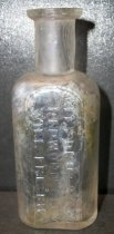 "Image of 1999.048.213 - Will Frisbie Medicine Bottle recovered from City Centre Plaza, c. 1880-1920. This bottle is oval shaped with a flat front face in cross section and it has narrowed slightly from shoulder to base. The rim has prescription finish which is narrow (vertically) and the outside surface distinctly tapers in from the top surface of the finish to bottom. The front side of bottle is an elaborate monogram of WF initials and a banner that outlines the name ""CITYDRUG STORE/REDWOOD CITY/ WILL FRISBIE"". A .75 inch short and narrow neck flares out .5 inch shoulders to a 2.25 inch body. The bottle is clear and shows evidence of glass machine manufacture"