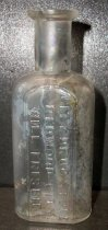 """Image of 1999.048.217 - Will Frisbie Medicine Bottle recovered from City Centre Plaza, c. 1880-1920. This bottle is oval shaped with a flat front face in cross section and it has narrowed slightly from shoulder to base. The rim has prescription finish which is narrow (vertically) and the outside surface distinctly tapers in from the top surface of the finish to bottom. The front side of bottle is an elaborate monogram of WF initials and a banner that outlines the name """"CITYDRUG STORE/REDWOOD CITY/ WILL FRISBIE"""". A .75 inch short and narrow neck flares out .5 inch shoulders to a 2.25 inch body. The bottle is clear and shows evidence of glass machine manufacture"""