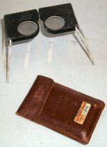 Image of 2014.022.002 - Abrams Instrument Company Pocket Stereoscope, c. 1944.  Pocket stereoscope (A) in leather case (B).  Pocket stereoscope (A) has two round glass lenses mounted inside black metal casing.  Casing for each lens slides on a metal bar inserted at the top to adjust for eye width.  On sides are mounted two hinged wire arms that have been painted white.  These fold over lenses for storage or open for viewing maps.  Pocket stereoscope is stored inside a brown leather case (B) with a snap closure.