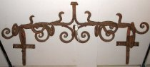 """Image of 2014.025.001 - Iron Coat or Hat Rack.  Ornate, wall-mounted coat rack is solid iron.   Overall design mimics the shape of a growing vine.  Main cross bar is comprised of two wavy """"vines"""" growing  towards the center from opposite directions and fusing to form a single vine which extends upwards.  On either side of this center branch are two smaller branches facing the middle.  Beneath this main bar extend five clusters of three curled branches each.  Coat rack is secured to the wall with cross brackets on either side, each with holes for wall screws."""