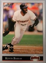 "Image of 2015.003.008 - Kevin Bass Baseball Card, 1992, Leaf paper card with Kevin Bass at home plate having just swung a bat and preparing to run to first base. There is no bat in his hands.  He is wearing a white uniform, with a black long-sleeved shirt underneath, black batting gloves and a black batting helmet with orange letters.  Text on black bar on bottom reads, ""Kevin Bass OF"" with the San Francisco Giants logo to the right.  In the upper left hand corner is the Leaf logo. The card has a silver border.  The back of the card has a silver background with black and white lettering.  The left side has a picture of Bass getting ready to catch a fly ball, he is wearing a white Giants uniform with a black long-sleeved shirt underneath, a light brown glove and a black baseball cap.  Text describes his biographical information, accomplishments and lists statistics from 1982 to 1991. Also contains logos for MLB, San Francisco Giants, and MLBPA as well as copyright information."
