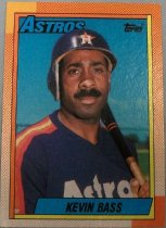 "Image of 2015.003.009 - Kevin Bass Baseball Card, 1990, Topps card with Kevin Bass on the front wearing a blue jersey with white letters and red, orange and yellow stripes on the sides, and dark blue cap with a white H superimposed over an orange star.  He is holding a baseball bat over his left shoulder.  The picture has a blue sky as the background and the edges have red dots superimposed on a background that fades from orange to white.  The top of the cards reads ""ASTROS"" in blue letters and has the Topps logo.  Text on blue bar reads, ""Kevin Bass"".  The back is dark yellow with white and black text. Text describes his achievements and list statistics from 1982 to 1989. Also contains copyright information."