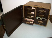 Image of 2015.009.002 - Barnett & Jaffe Photographic Slide Case, c. 1950-1955.  Locking case is made of wood covered with brown and gold colored diagonally striped paper.  Case opens in front to reveal two rows of four drawers each.  Front of drawers are covered in brown paper and have thin metal handles and a tiny label slot in the front.  Drawer itself is brown colored plastic with 30 slots to hold horizontal-shaped three-dimensional slides.  Case has no handle and has four plastic feet on the bottom.  When accessioned, some drawers contained slides and paper notes describing slide provenance.