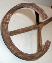 Image of 1975.226.001 - Coburn Branding Iron, c. 1872-1916. Cylindrical metal rod extends length of tool.  Metal rod splits into three metal tongs.  Three metal tongs attach to rounded, C-shaped brand.  Top of metal handle is shaped in a ring.  Cylindrical rod is slightly curved from use.