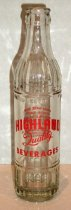 Image of 1986.232 - Highland Soda Bottle, c. 1931-1944. Clear glass bottle. Cylindrical shape. Two seams that extend along length of bottle to neck. Vertical ribbing on bottom band with a horizontal raised ring above. Large smooth band with printed red text and embossed text. Horizontal raised ring with vertical ribbing above. Body tapers to narrow smooth neck. Neck tapers to bulbous mouth which tapers to rounded lip. Bottle is empty. Air bubbles throughout base of glass.