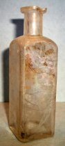 Image of 1999.048.355 - Medicine Bottle recovered from City Centre Plaza, c. 1870-1920. This bottle is square shaped in cross section and it has narrowed slightly from shoulder to base. The rim has prescription finish which is narrow (vertically) and the outside surface distinctly tapers in frFom the top surface of the finish to bottom.  A .875 inch short and narrow neck flares out .75 inches shoulders to a 3.75 inch body. The base is shaped like square with a concave circle. The bottle is clear and shows evidence of glass machine manufacture.