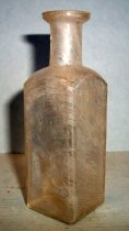 Image of 1999.048.358 - Medicine Bottle recovered from City Centre Plaza, c. 1870-1920. This bottle is square shaped in cross section and it has narrowed slightly from shoulder to base. The rim has prescription finish which is narrow (vertically) and the outside surface distinctly tapers in frFom the top surface of the finish to bottom.  A .75 inch short and narrow neck flares out .75 inches shoulders to a 2.875 inch body. The base is shaped like square with a concave circle. The bottle is clear and shows evidence of glass machine manufacture.