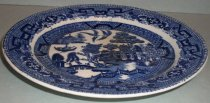 Image of 1999.054.006 - Blue Willow Semi China Dessert Plate, 1832.  White shallowplate a flat bottom that curves up to a horizontal rim.  It has a blue transfer design of imagery depicting structures, a bridge, grass and trees in the center on the top side.  It has an outer border just outside the imagery and along rim of a geometric motif.  Back side is solid white with blue Ridgeway Semi China maker's mark.