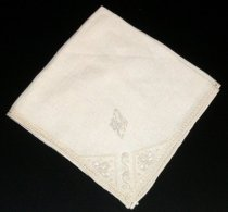 """Image of 2010.092.032B - Holbrook-Palmer Napkin, c. 1926-1958. Holbrook-Palmer Collection. Square beige-colored linen napkin with cream-colored drawn thread work edging.  Cream-colored dran stitch work and satin stitched floral designs.  Satin-stitched initials """"OPH"""" in diamond shape above floral designs."""
