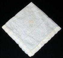 "Image of 2010.092.034A - Holbrook-Palmer Handkerchief, c. 1926-1958. Holbrook-Palmer Collection. Square beige-colored linen handkerchief with cream-colored hemstitch edge. Openwork inside edges of napkin create design. Cream-colored satin stitched shield with initials topped by crown in corner.  Initials read ""OPH"" ."