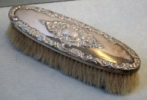 "Image of 2012.015.006C - Clothes Brush, c. 1852-1894. Silver elongated oval clothes brush with bristles protruding outward from wooden base.  Floral embossed designs on silver along edge and in center.  Engraved monogram ""FWS"" on oval base inside of center floral design."