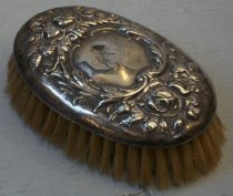 "Image of 2012.015.006D - Clothes Brush, c. 1860-1940. Oval sterling silver clothes brush with floral embossed design. The floral design is embossed in a ring around the edge. The floral embossed design encircles a monogram reading, ""HSH"". Set inside the oval sterling silver is a wooden base for the bristles. Yellow bristles protrude outward from wooden base."