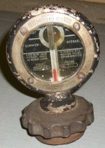 Image of 2013.007.010 - MotoMeter Radiator Cap, August 13, 1918. Cylindrical screw cap with protruding tube thermometer that extends length of radiator cap.  Top of screw cap is scalloped.  Top of cap has raised metal ring that attaches circular glass-front gauge.  Edges of gauge are framed in painted black metal.  Another steel metal frame with engraved text, secured with four screws, holds glass front and back. Beneath glass is gauge told you temperature of water in radiator. Radiator cap used on a Ford Model T.