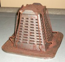 Image of 2013.007.018 - Stovetop Toaster, n.d. Square metal base with four sides that travel upward in a pyramid shape ending in finished squared top. Inside of pyramid shape is hollow. Four side have two vertical metal wires with an outward bulge at bottom, to lean slices of bread against pyramid walls. Wire attached to bent metal lip on top piece. Four columns of horizontal vents, for toasting, on each of the four sides of the pyramid walls.