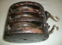Image of 2013.017.025 - Three Pulley Block and Tackle, n.d. Painted black wooden tackle that is oval cylindrical in shape. Three metal pulley rings inside wooden frame. Rings are attached by a metal rod that extends the length of the tackle. Metal half circles at top of pulley are broken off and missing. Two steel J-hooks attached with bolts to the half circle metal pieces.