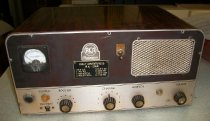 Image of 2013.017.026 - Marine Corps. Ship's Radio, c. 1950s. Rectangular box radio. Covered on top and sides with wood paneling. Back of radio has metal backing with vents and partial wiring, broken off and missing. Lower portion of front metal panel has four knobs and two light bulbs. As well as a power jack and a transmit switch on the left side. Top half of metal panel has a gage and speaker with metal grate. Front also has a panel with engraved text and a speaker switch.