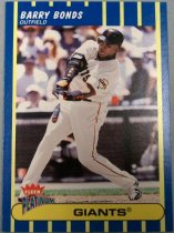 "Image of 2015.003.031 - Barry Bonds Baseball Card, 2003, Fleer paper card.  The front of the card has blue and yellow vertical stripes surrounding an image of Barry Bonds swinging a baseball bat.  He is wearing a white San Francisco Giants uniform with a black batting helmet, black elbow guard on his right arm, black and orange wrist bands and batting gloves.  Text on the front reads ""BARRY BONDS OUTFIELD"", and includes Fleer and the Giants' logos.  The back of the card has white and blue vertical stripes with text that describes Barry Bonds' statistics, achievements and biographical information.  The back also includes Fleer, Giants, MLB and MLBPA logos as well as copyright information."