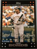 Image of 2015.003.032 - Barry Bonds Baseball Card, 2007, Topps paper card.  The front of the card has an image of Barry Bonds with a black border around it.  He is wearing a white San Francisco Giants uniform, with black batting helmet, black wristbands, black, white and grey batting gloves, and a black elbow guard on his right arm.  He is holding a baseball and the background is of the stands and a dugout.  The image has Barry Bonds' signature.  The back of the card has a black border surrounding a yellow-green box.  Text on the back lists his achievements, statistics and biographical information.  Also includes the Giants, MLB, MLBPA and Topps logos as well as copyright information.