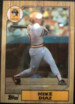 Image of 2015.003.035 - Mike Diaz Baseball Card, 1987, Topps paper card.  The front of the card has a border that is wooden in appearance.  The Pirates logo is in the upper left corner and the Topps logo is in the lower left corner.  The front of the card has an image of Diaz swinging a baseball bat during a game.  He is wearing a grey Pittsburgh Pirates uniform with black and yellow stripes and a yellow batting helmet with a black bill.  The back of the card is yellow and text lists his biographical information, statistics and accomplishments.  Also includes copyright information.