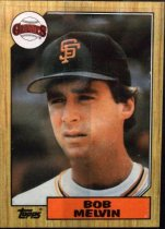 "Image of 2015.003.046 - Bob Melvin Baseball Card, 1987, Topps paper card.  The front of the card has an image of Melvin wearing a white San Francisco Giants uniform with orange, white and black stripes around the collar.  He is also wearing a black baseball cap with an orange interlocking ""SF"".  The Giants logo appears in the upper left corner and the Topps logo in the bottom left corner.  Text in an orange box at the bottom edge reads, ""BOB MELVIN"".  The front of the card has a border that is wooden in appearance.  The back of the card is yellow and lists Melvin's biographical information, statistics and accomplishments.  Also includes the Topps logo as well as copyright information."