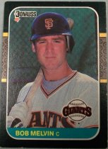 "Image of 2015.003.047 - Bob Melvin Baseball Card, 1986, Donruss paper card.  The front of the card has an image of Melvin with a black border.  He is wearing a white San Francisco Giants uniform with black and orange stripes and letters.  He is also wearing a black batting helmet with an orange 'SF' and is holding a baseball bat over his right shoulder.  Text reads, ""BOB MELVIN c"".  Also includes Donruss and Giants logos.  The back of the card is orange-yellow with a white box.  Text describes Melvin's biographical information, statistics and accomplishments.  Also includes MLB and MLBPA logos as well as copyright information."