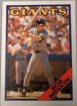 "Image of 2015.003.048 - Bob Melvin Baseball Card, 1988, Topps paper card.  The front of the card has an image of Melvin with a white border.  He is wearing a grey San Francisco Giants uniform with black and orange stripes and letters and a black batting helmet.  He standing in the batter's box during a game and is in a batting stance. Text reads, ""GIANTS"" and ""BOB MELVIN"".  Also includes Topps' logo.  The back of the card is orange-brown with black text.  Text describes Melvin's biographical information, statistics and accomplishments.  Also includes copyright information."