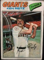 "Image of 2015.003.049 - Ken Reitz Baseball Card, 1977, Topps paper card.  The front of the card has an image Reitz holding a baseball bat and posing as if he just swung it, the bat is behind his head.  He is wearing a white San Francisco Giants uniform with black and orange stripes on the sleeves, a black belt and a black baseball cap with an orange interlocking ""SF"".  His is standing in an empty stadium with a batting cage visible.  His signature is at the center of the card near his belt.  Text on the front of the card reads, ""GIANTS KEN REITZ 3rd BASE"".  The card has a white border.  The back of the card is brown with green text.  The text lists his biographical information, statistics and accomplishments.  Also includes copyright information."