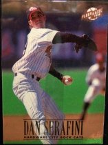 "Image of 2015.003.051 - Dan Serafini Baseball Card, 1996, Fleer paper card.  The front of the card has an image of Serafini wearing a white pinstriped New Britain Rock Cats uniform.  He is also wearing a blue long-sleeve shirt and a blue baseball cap with a red bill and the Rock Cats logo.  The image is of him pitching during a game.  He is getting ready to throw the ball, his left hand is behind him throwing the ball and his right hand is in front wearing a black glove.  An infielder is visible in the background.  In the upper right corner is a gold Fleer logo.  Text in gold reads ""DAN SERAFINI HARDWARE CITY ROCK CATS"".  The back of the card was unable."