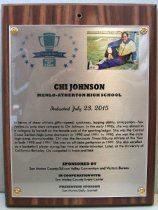 "Image of 2015.016.005 - Plaque commemorating Chi Johnson of Menlo-Atherton High School being inducted into the San Mateo County Sports Hall of Fame on July 23, 2015.  The plaque is silver acrylic mounted with golden screws onto a dark wooden base.  Plaque includes image of Johnson sitting on a grass field with her left leg out in front of her and her right knee bent.  She is wearing a blue and yellow track suit.  A brief biography is also on the front, ""In terms of sheer athletic gifts-speed, quickness, leaping ability, anticipation-few  /  Peninsula prep stars compare to Chi Johnson.  In the early 1990s, she was almost in  /  a category by herself on the female side of the sporting ledger.  She was the Central  /  Coast Section high-jump champion in 1990 and 1991.  In 1990, she won the state  /  high-jump championship.  Chi was the Peninsula Times-Tribune Athlete of the Year  /  in both 1990 and 1991.  She was an all-state performer in 1991.  She also excelled  /  as a basketball player during her time at Menlo-Atherton.  Later, at the University of  /  California-Berkeley, Chi competed in track and field.""  The back of the plaque has an oval sticker with the logo and contact information for Spotlight Impressions, the manufacturer of the plaque."