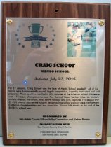 """Image of 2015.016.007 - Plaque commemorating Craig Schoof of Menlo School being inducted into the San Mateo County Sports Hall of Fame on July 23, 2015.  The plaque is silver acrylic mounted with golden screws onto a dark wooden base.  Plaque includes image of Schoof wearing a white baseball uniform with blue letters and numbers, a blue belt, a blue baseball hat, sunglasses and a blue undershirt.  He is at a baseball field, standing in front of a green wall and he is pointing with his left and right index fingers.  A brief biography is also on the front, """"For 27 seasons, Craig Schoof was the face of Menlo School baseball.  All of his  /  teams were fundamentally sound, highly competitive, superbly motivated and well-  /  prepared.  Those qualities resulted in 494 victories at the Atherton school.  His teams  /  won 17 league championships and five Central Coast Section titles.  As Menlo's  /  athletic director, the school, in all sports for boys and girls, captured 121 league and  /  32 CCS crowns; also on the Knights' ledger during Schoof's tenure were 16 Northern  /  California championships and two state titles.  Schoof left Menlo at the end of the  /  2013-14 school year.""""  The front of the plaque also has the Sports Hall of Fame logo as well as sponsoring information.  The back of the plaque has an oval sticker with the logo and contact information for Spotlight Impressions, the manufacturer of the plaque."""