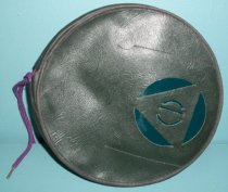 Image of 1964.185 - Headlight Blackout Cover, c. 1939-1945 (WWII). Round dark green leather circle with black leather hem on edge.  Black fabric flaps protrude outward from back of round circle to cover headlight lens.  Round seam runs around length of circle with purple cloth shoestring to adjust size.  Front of circle has cutout shape of a triangle within a circle.  The center of the triangle has a cutout circular shape with a line through the center.  Two stitched seams run along sides of the cutout shaped.  Between the cutout shapes is a dark teal cloth covering.  The underside of the round disk is covered with a green cloth material.