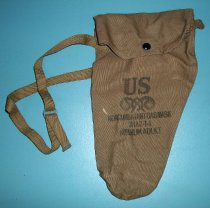 Image of 1972.514.002 - Gas Mask Canvas Case, c. 1939-1945. Cylindrical canvas bag with stamp printed text on front to hold gas mask. Canvas bag widens at top with canvas flap and metal button closure.  Canvas strap sewn to either side to attach.  Metal buckles on canvas strap for adjusting length.  Metal hem edge on end of canvas strap. Bottom of bag has metal eyelet. All pieces olive green drab in color.