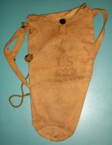 Image of 1982.001.002 - Gas Mask Canvas Case, c. 1939-1945. Cylindrical canvas bag with stamp printed text on front to hold gas mask. Canvas bag widens at top with canvas flap and metal button closure.  Canvas strap sewn to either side to attach.  Metal buckles on canvas strap for adjusting length. Canvas cord sewn into side of canvas bag and attached on the other side to a rectangular metal ring.  Cord has a metal aglet at the end.  Cord is knotted to adjust size/length. All pieces tan in color.