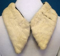 Image of 1988.082 - Ermine Fur Collar, n.d. White fur collar is rectangular in shape with black velvet lining. The collar gradually expands in width to the ends. The ends of the collar are angled outward. There are two slits extending the width of the collar on the proper left side.