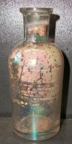 Image of 1999.048.330 - Medicine Bottle recovered from City Centre Plaza, c. 1830-1920. This bottle is round shaped.  The rim has prescription finish which is narrow (vertically) and the outside surface distinctly tapers in from the top surface of the finish to bottom. The bottle is clear and shows evidence of glass machine manufacture.