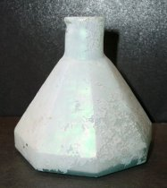 Image of 1999.048.346 - Umbrella ink bottle recovered from City Centre Plaza, c. 1840-1909. This bottle is conical in shaped with eight-sided panels to form the sides, hand-blown tooled rim for a crudely rolled or folded-in finish. A .25 inch short neck flares out to a .75 inch double ring shoulder to a 2.25 inch body. The bottle is clear and shows evidence of glass hand-made manufacture.