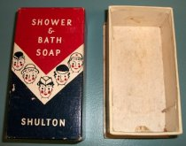 "Image of 2000.021.009 - Shower and Bath Soap Box, c. 1941-1945. The box is composed of a rectangular bottom (B) and top (A) that is made of cardboard and covered with printed paper. The box has a rectangular lid (A) that the top is red and the middle has a chevron white stripe with painted faces and a blue bottom. There are five painted faces along front and three on each side. Each of the faces are wearing various hats and all have round eyes, rosy cheeks, and red lips. Front of box reads, ""SHOWER  /  &  /  BATH  /  SOAP  /  SHULTON"". Interior of box is white. The bottom of box (B) is rectangular in shape and is white. The bottom of box has an extended lip along the bottom. The box is empty. (Possibly a nurse's soap?)"