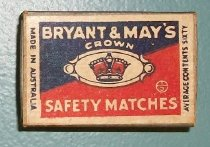 """Image of 2000.021.018 - Bryant & May's Matchbox, c. 1941-1945. Rectangular cardboard box with a sliding cardboard drawer filled with matches. Box has a paper label with text reading, """"BRYANT & MAY'S  /  CROWN  /  SAFETY MATCHES"""" and an image of a crown. The top and bottom side has a purple striking paper, to light match. Bottom and sides of sliding drawer are a green color."""