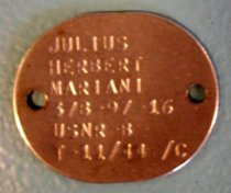 Image of 2000.021.024 - Julius Herbert Mariani Military Dog Tag, 1944. Flat oval silver metal military tag with stamped text on front. Two holes on each and of tag.