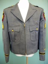 "Image of 2009.004.011 - San Mateo County Sheriff Jacket, c. 1960, n.d. Long sleeve zip-up jean jacket with blue satin lining. The front of the jacket has a bellow pleated pocket on each side. The pockets are lined with the blue satin fabric and have a gold embossed button in the center with a snap button on both of the corners of the flap. The gold buttons are embossed with text reading, ""EUREKA  /  CALIFORNIA"" and have a small embossed portrait. The zipper on the front of the jacket is placed in the center and is gold. Above the proper left side pocket there is a rectangle jean patch with a grommet at the top and bottom of the patch. Above the zipper is a collar with a notched lapel. The shoulders of the jacket have an epaulet on each side with a gold embossed button and a triangular end. The top of the sleeves have a shield shaped patch that reads, ""SHERIFF  /  SAN MATEO  /  COUNTY"" and a sergeant gold-on-black chevron patch. The bottom of the sleeves have a black band with gold trim sewn width-wise on the outer-half of the sleeve. Above the band, on the proper left sleeve there are two embroidered gold stars. The jacket has a half belt sewn into the waist. A waist strap with triangular trim are sewn to each side with two plastic blue buttons sewn to the jacket, to adjust waist size. Inside the jacket there is a slit pocket in the proper right side and above the pocket there is a black cloth label with white stitching that reads, ""MC"". At the top of the lining there is a black cloth strap, to hang jacket."