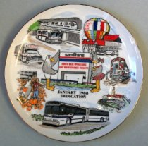 """Image of 2015.019.002 - SamTrans Dedication Plate, January 1988.  White glazed porcelain plate has gold paint along outer edge.  Front of plate is painted with imagery depicting the samTrans North Base Operation and Maintenance Facility in the center with two seagulls standing on either side.  Clockwise, beginning at 1:00 O'clock on front of plate is an image of the building with a bus out front and a balloon on the roof with a sign that says, """"HERES  /  THE  BASE""""; a train breaking through a banner held by two figures which says, """"samTra … THE 'NEW CALTRAIN""""; an image of the football field at Stanford University; a two section bus; a pumpkin patch with a bus in the background; a """"REDI-WHEELS"""" camper-style bus, and a bus parked beneath a BART  train.  In center below image of building is printed, """"JANUARY 1988  /  DEDICATION.""""  Back of plate has dedication """"to the memory of John T. Mauro, First General Manager of the District, for his foresight and vision for public transit."""""""