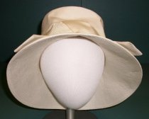 "Image of 2015.020.002 - I. Magnin & Co. Wide-brimmed Hat, c. 1940s-1960s.  White sunhat (?) is comprised of a linen-weave polyester.  Round crown is flat on top with straight 4"" sides.  Brim comes out at an angle from crown and has two layers of fabric that have been stitched in concentric circles to keep firm.  A 2"" white ribbon forms a band just above brim ending in an upside-down V-shape at front of hat.  A taupe or light brown-colored ribbon is sewn to interior where brim meets crown."