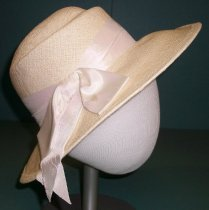 "Image of 2015.020.005 - Betmar Sunhat, c. 1940s-1960s. White colored wide brimmed hat is comprised of a woven straw-like material that has a slight sheen.  Crown has straight sides and a rounded top that is slightly creased.  A white satin ribbon forms a band around crown at brim and ends in a large bow at the proper right side of hat.  Hat is completely woven with the brim turned up at edge and sewn flat, forming a hemmed edge.  ""Betmar"" label is sewn to interior."