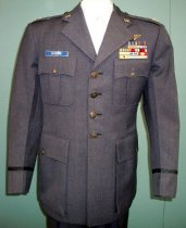 """Image of 2015.025.001A - US Air Force Dress Uniform Jacket, c. 1952-1982.  Long blue-colored wool jacket has two pleated chest pockets with button flaps, two straight lower front pockets with button flaps, an interior straight chest pocket with horizontal opening on proper right, epaulet straps secured with buttons beneath the collar and a four-button front closure.  All buttons are pewter-colored metal with embossed eagle.  There is dark blue-colored ribbon banding 3"""" above bottom of sleeve.  There is a split in the back just below the belt.  Jacket interior is lined with blue-colored rayon.  Several badges and emblems decorate the coat:  silver-colored metal maple leaves on each epaulet at shoulder; """"U.S."""" silver-colored metal pins on top notches of collar; silver-colored metal wings on proper left breast; various cloth-colored bars above left breast pocket representing various tours of duty and accomplishments with the air force; blue white plastic name tag above proper right breast pocket with """"BROWN"""" engraved into it."""