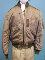 """Image of 2015.025.014 - Korean War US Airforce Flying Jacket,  c. 1950-1952.  Rayon(?) jacket is khaki on the outside with an olive colored rayon(?) lining and olive-colored knit collar, sleeves and waist.  Two front pockets above waist have diagonal snap flap closures.  Proper left arm has zippered side pocket below shoulder.  Four additional narrow pockets are sewn onto outside of side pocket for holding pens or items of similar shape.  Jacket has a front zipper closure with a snap at the waist.  Both zippers have brown leather handles attached to metal zipper handle.  Above proper left pocket is sewn a leather label in which """"A.R. BROWN"""" is stamped.  To the left of the label and pocket flap is sewn a vertical rectangle of brown leather.  Jacket has epaulet straps at shoulders with pointed snap closures at collar."""