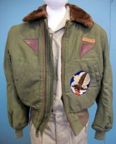 """Image of 2015.025.015 - WWII Army Air Forces Flying Jacket, c. 1942-1946.  Cotton olive-colored jacket has a brown wool fur lining and brown faux fur collar collar with olive colored knit sleeves and waist.  An additional rectangle of faux fur is sewn to back of collar and can be buttoned when collar is raised for added warmth to one's neck.  Two front pockets above waist have diagonal snap closures.  There also two interior pockets with vertical snap closures.  Proper left arm has four narrow pockets for holding pens or items of similar shape.  Jacket has a front zipper closure.  Above proper left pocket is sewn a leather label in which """"A.R. BROWN"""" is stamped.  Below the label a brown leather triangle is sewn.  Left proper shoulder has the Army Air Forces insignia (blue circle with wings and a white star with a red circle in its center) died into the fabric.  A large patch of an eagle carrying two red bombs with a white cloud, blue sky and gold lightning bolt is sewn onto proper left.  Eagle patch is from when Allan R. Brown served on the 731st Bomb Squadron, indicating that he wore this jacket both during WWII and during the Korean War."""