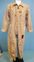 "Image of 2015.025.019 - WWII Army Air Force Flying Suit c. 1942-1946 worn by Allan R. Brown during World War II..  Khaki-colored cotton jumpsuit or coveralls consists of one-piece pants and jacket with collar and a zipper front from the waist to the collar.  Long sleeves have button cuffs.  Bottom of legs have zipper closures.  There are small straps with buttons at waist.  There are four khaki-colored metal grommets in each arm hole for ventilation.  There two breast pockets with diagonal zippered closures and deep front pockets at waist with side-slit openings.  Front of pant legs have pockets with side zipper closures at thy and pockets with top zipper closures at outside of shin.  Proper left arm has four narrow pockets for holding pens or items of similar shape.  A brown leather clip  is affixed to top proper left pants pocket.  Proper left front pocket is stamped with ""B-7173"" and a brown leather ""A.R. BROWN"" label is sewn just above pocket.  Army Air Forces logo (blue circle with wings and a white star with a red circle in center) is died into fabric of proper left shoulder."
